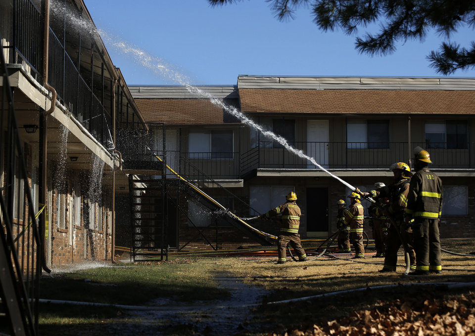 Firefighters are shown Wednesday in Midwest City at the Eden Cove Apartments, where a fire left seven families homeless. Photo by Garett Fisbeck, For The Oklahoman <strong>Garett Fisbeck</strong>