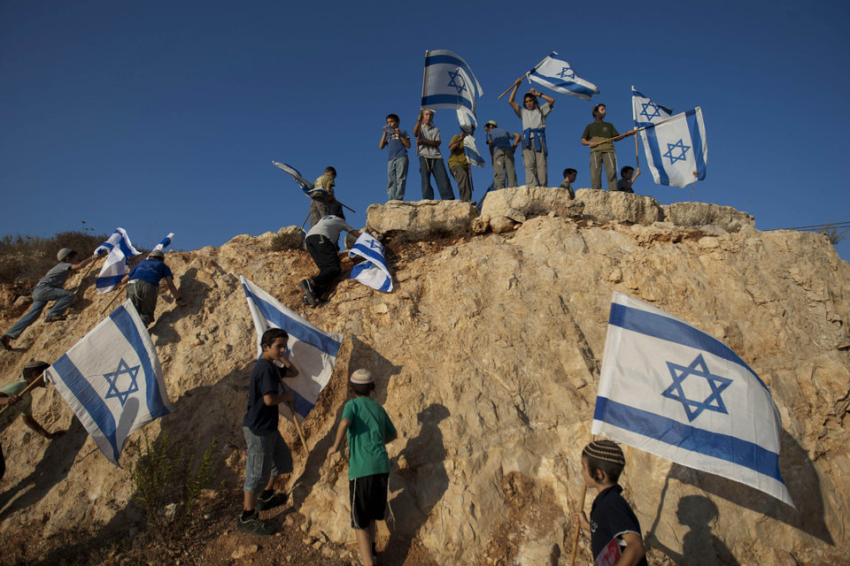 Photo - File - In this Sept. 20, 2011file photo, Israeli settler youths wave Israeli flags at the start of a protest march against Palestinian statehood, from the West Bank Jewish settlement of Itamar near the Palestinians town of Nablus. Palestinian Israel is going ahead with plans to build more than 1,000 settler homes in the West Bank, a spokesman said Thursday, a step that drew criticism from the Palestinians and may pose a challenge to peace efforts by Secretary of State John Kerry. (AP Photo/Ariel Schalit, File)