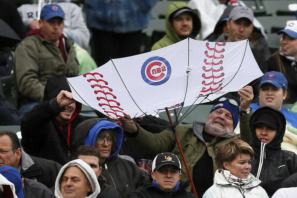Photo - A fan has his umbrella flipped inside out by the wind during the fifth inning of a baseball game between the Chicago Cubs and the Milwaukee Brewers on Friday, May 16, 2014, in Chicago. (AP Photo/Andrew A. Nelles)