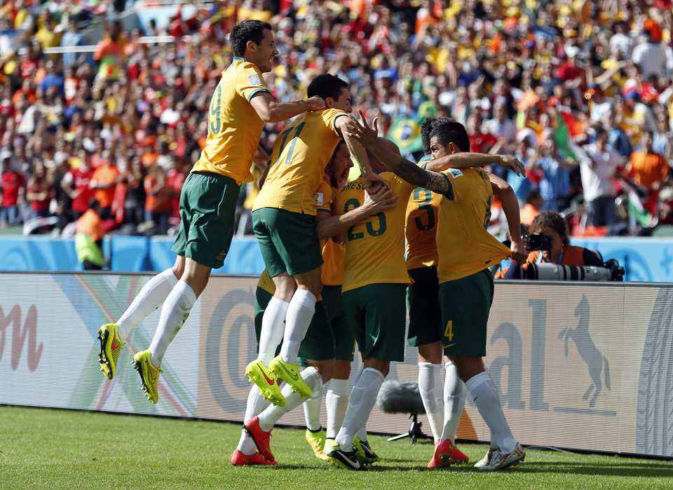 Photo - Australian players celebrate after Tim Cahill, right,  scored his side's first goal during the group B World Cup soccer match between Australia and the Netherlands at the Estadio Beira-Rio in Porto Alegre, Brazil, Wednesday, June 18, 2014.   (AP Photo/Wong Maye-E)