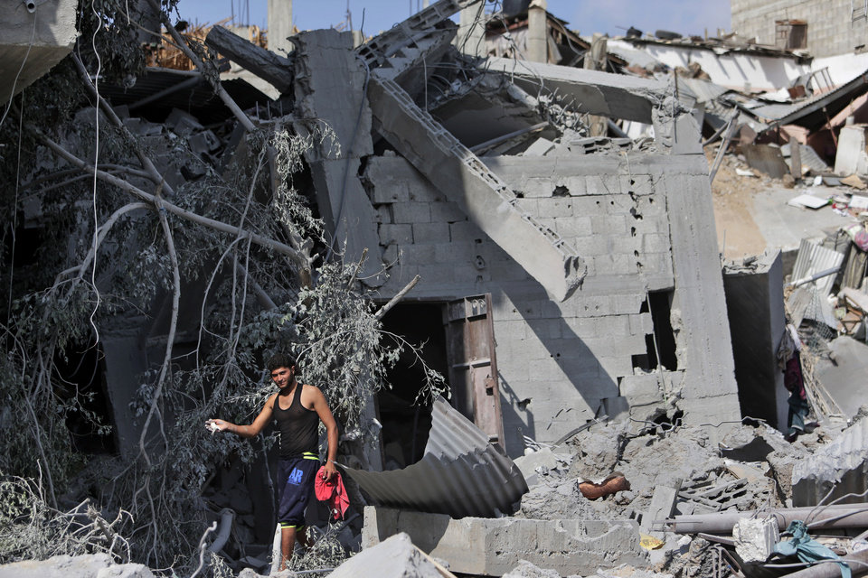 Photo - A Palestinian shows his pet bird which he managed to catch amid the rubble of houses destroyed by Israeli strikes in Beit Hanoun, northern Gaza Strip, Sunday, July 27, 2014. Hamas on Sunday agreed to observe a 24-hour humanitarian truce ahead of a major Muslim holiday after initially rejecting such an offer by Israel, as the two sides wrangled over setting the terms of a lull the international community hopes can be expanded into a more sustainable truce. (AP Photo/Lefteris Pitarakis)