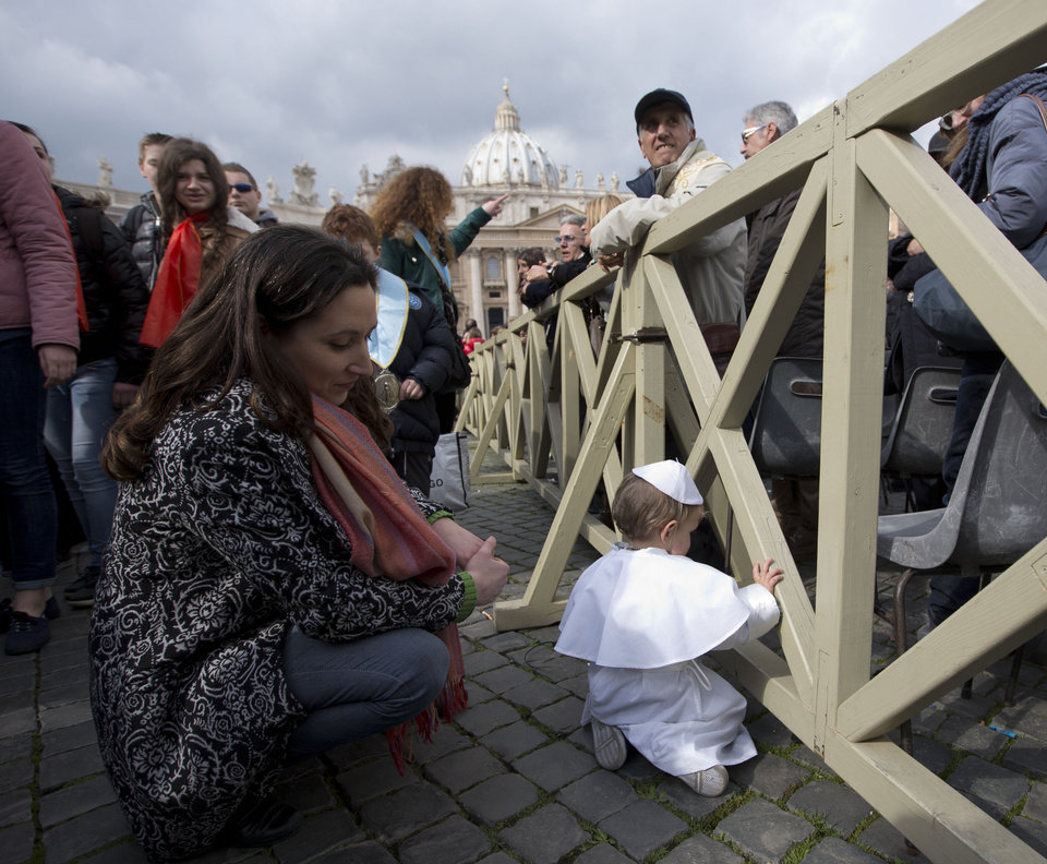 Photo - Paola Ciabattini looks at her 19-month-old son Daniele De Sanctis, dressed up as a pope, during Pope Francis' weekly general audience in St. Peter's Square at the Vatican, Wednesday, Feb. 26, 2014. Francis kissed the child as the new must-have Carnival costume made its debut at the pope's general audience Wednesday. Daniele, who was crying, was hoisted up to Francis as he drove by in his open-topped jeep. During Carnival in Italy, children often go to school and spend their weekends dressed up in pirate, princess — and now pope — costumes. Carnival, also known as mardi gras, marks the period before the church's solemn Lenten season begins. Ciabattini said she dressed her son as a pope in a demonstration of affection towards Pope Francis. (AP Photo/Alessandra Tarantino)