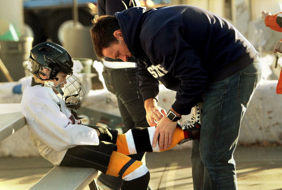 Scott Kilgore helps son Ty, 7, suit up for an ice hockey game Saturday at the Norman Outdoor Holiday Ice Rink at Interstate 35 and Lindsey Street. PHOTOS BY STEVE SISNEY, THE OKLAHOMAN