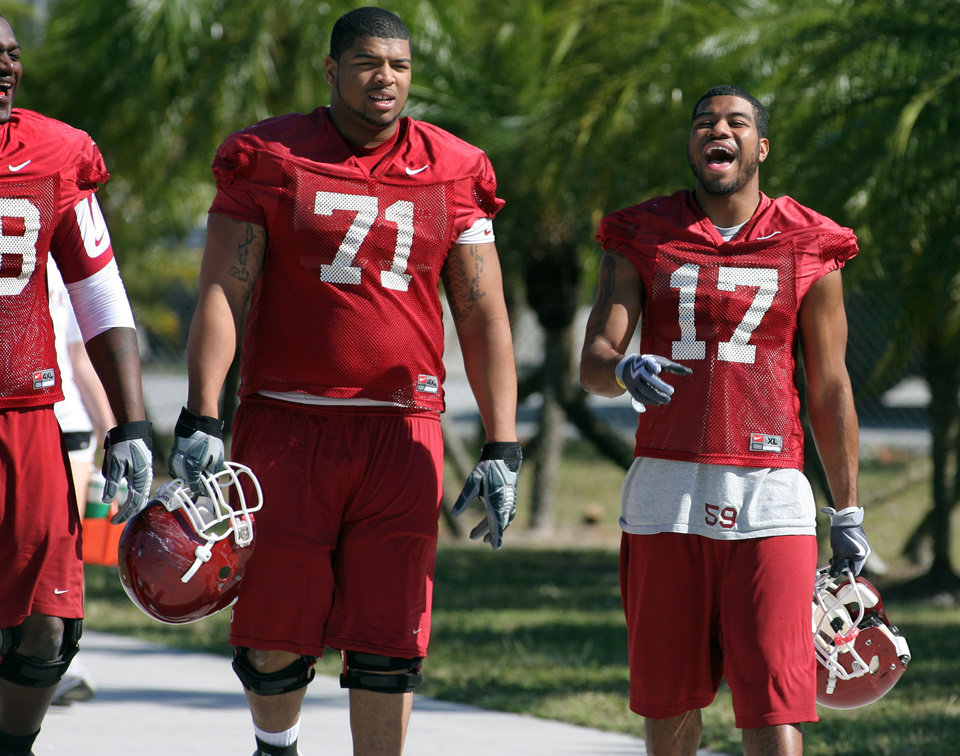 Photo - UNIVERSITY OF OKLAHOMA / OU / BOWL CHAMPIONSHIP SERIES / BOWL GAME / COLLEGE FOOTBALL / BCS NATIONAL CHAMPIONSHIP GAME: Oklahoma running back Mossis Madu right, enjoys a laugh with offensive lineman Trent Williams as they walk out to football practice Barry University in Miami, Saturday Jan. 3, 2009. Oklahoma plays Florida in the BCS Championship NCAA college football game on Thursday, Jan. 8. (AP Photo/Jeffrey M. Boan) ORG XMIT: FLJB106