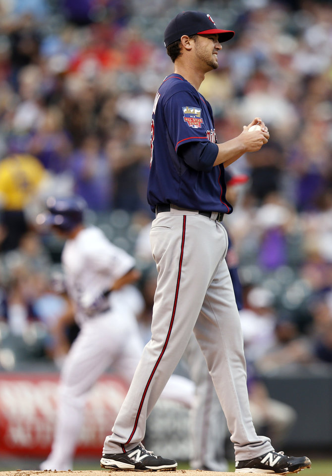 Photo - Minnesota Twins starting pitcher Kris Johnson reacts to giving up a two run home run to Colorado Rockies' Drew Stubbs against the Colorado Rockies during the first inning of a baseball game on Friday, July 11, 2014, in Denver. (AP Photo/Jack Dempsey)