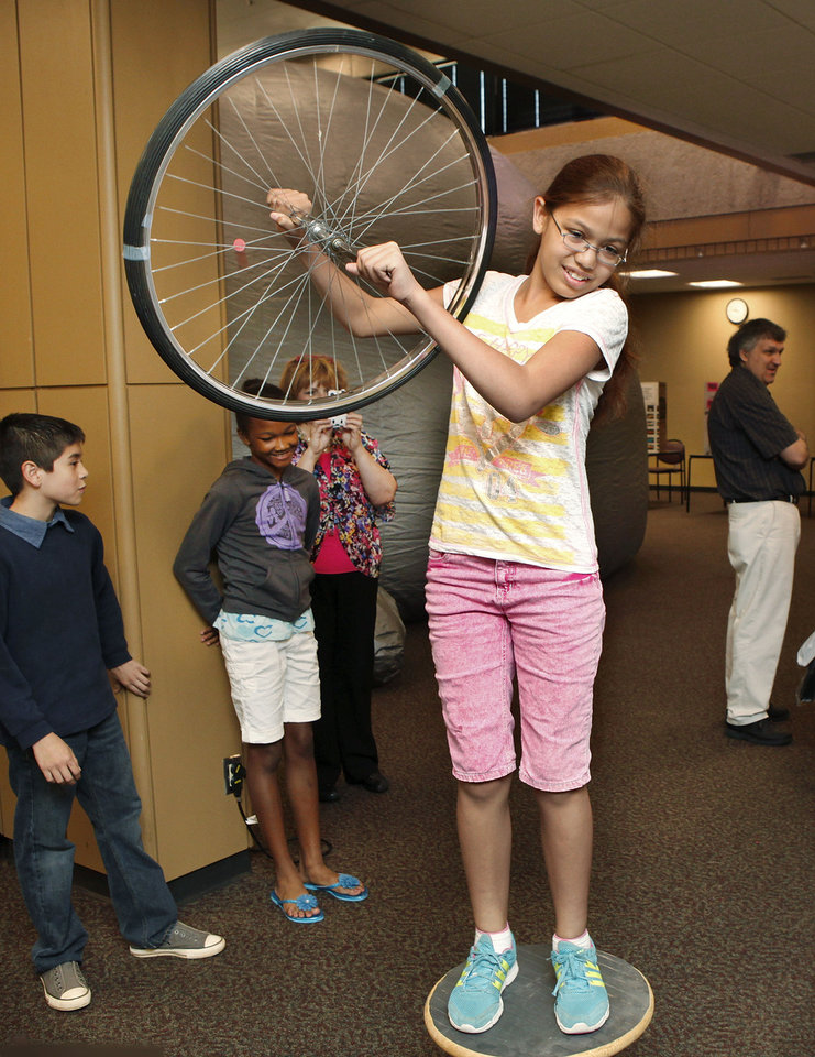 Photo - Rekiyah Esquibel, a fifth trade student at Pleasant Hill School, stands on a mobile platform while holding a spinning bicycle tire at a booth organized by students from the Rose State College physics department. Students learned that as they held the spinning tire at varying angles, their body and the platform would move accordingly.  The college students were using the apparatus to illustrate  the principle of transfer of motion, said Ron Perez-Guerra, a physics student.  This was at the Central Oklahoma Science and Engineering Festival,  hosted by Rose State College at its Midwest City campus on Wednesday,  April  25, 2012.        Photo by Jim Beckel, The Oklahoman
