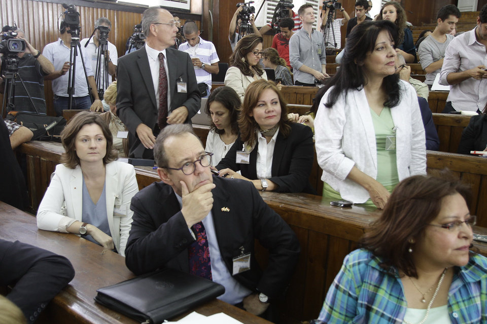 Photo - The Canadian ambassador to Egypt, David Drake, center, watches proceedings in a sentencing hearing for Al-Jazeera journalists, in a courtroom in Cairo, Egypt, Monday, June 23, 2014. An Egyptian court on Monday convicted three journalists from Al-Jazeera English and sentenced them to seven years in prison each on terrorism-related charges, bringing widespread criticism that the verdict was a blow to freedom of expression. The three, Australian Peter Greste, Canadian-Egyptian Mohamed Fahmy and Egyptian Baher Mohammed, have been detained since December charged with supporting the Muslim Brotherhood, which has been declared a terrorist organization, and of fabricating footage to undermine Egypt's national security and make it appear the country was facing civil war.  (AP Photo/Ahmed Abd El Latif, El Shorouk Newspaper) EGYPT OUT