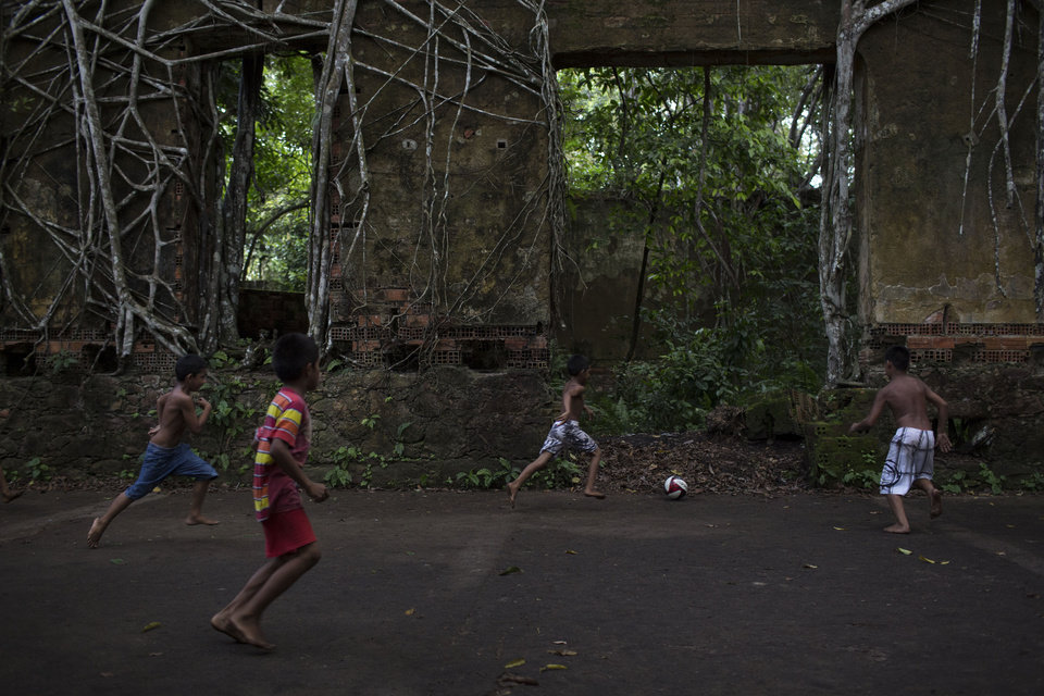 Photo - In this May 21, 2014 photo, Children play soccer in the ruins of Paricatuba, near Manaus, Brazil. Paricatuba was built in 1898 at the height of the region's rubber boom, which briefly transformed Manaus into one of the richest cities in the world. After the Italian migration dried up, the villa housed an art school run by French priests. Then it became a penitentiary. Then a leper colony, before simply being abandoned to the tropical elements. (AP Photo/Felipe Dana)