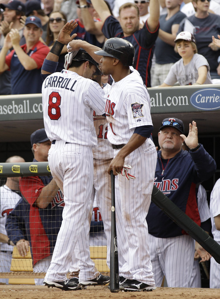 Minnesota Twins' Jamey Carroll, left, is greeted by teammate Ben Revere after scoring on a single by Pedro Florimon in the seventh inning of a baseball game Sunday, Sept. 30, 2012 in Minneapolis. At right is manager Ron Gardenhire. The Tigers won 2-1. (AP Photo/Jim Mone)