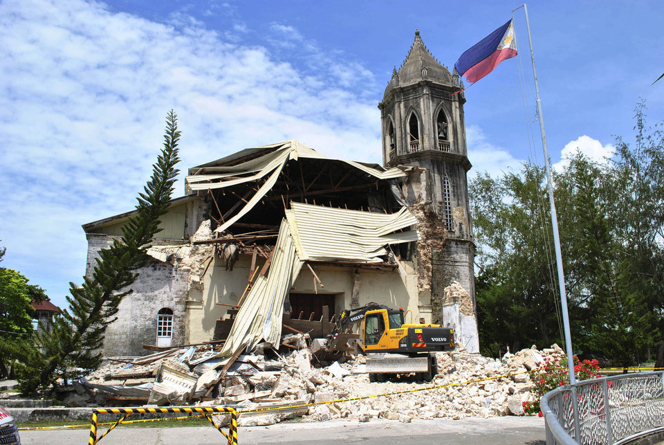 Photo - A crane shifts through the rubble of the damaged Our Lady of Assumption Parish church following a 7.2-magnitude earthquake, at Dauis in Bohol, central Philippines, Tuesday Oct. 15, 2013. The tremor collapsed buildings, cracked roads and toppled the bell tower of the Philippines' oldest church Tuesday morning, causing multiple deaths across the central region and sending terrified residents into deadly stampedes. (AP Photo)