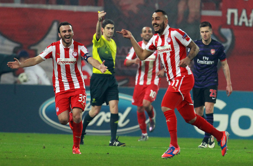 Olympiakos\' Kostas Mitroglou, right, celebrates with Vassilis Torossidis, left, after scoring against Arsenal during a group B Champions League soccer match in the port of Piraeus, near Athens, Tuesday, Dec. 4, 2012. (AP Photo/Thanassis Stavrakis)
