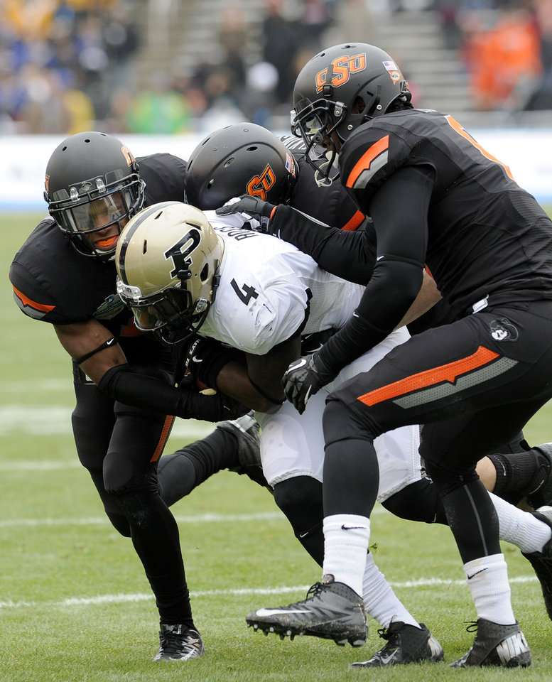 Photo - From left, Oklahoma State cornerback Kevin Peterson, linebacker Alex Elkins and safety Daytawion Lowe tackle Purdue wide receiver O.J. Ross (4) in the first half of the Heart of Dallas Bowl NCAA college football game, Tuesday, Jan. 1, 2013,in Dallas. (AP Photo/Matt Strasen)