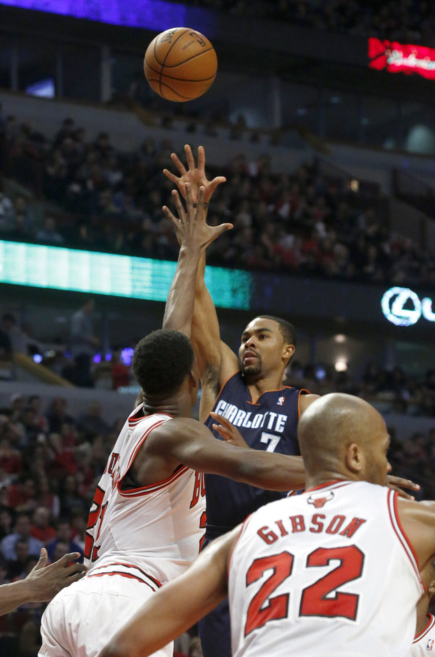 Charlotte Bobcats guard Ramon Sessions, center, shoots over Chicago Bulls' Jimmy Butler (21) and Taj Gibson during the first half of an NBA basketball game Monday, Dec. 31, 2012, in Chicago. (AP Photo/Charles Rex Arbogast)