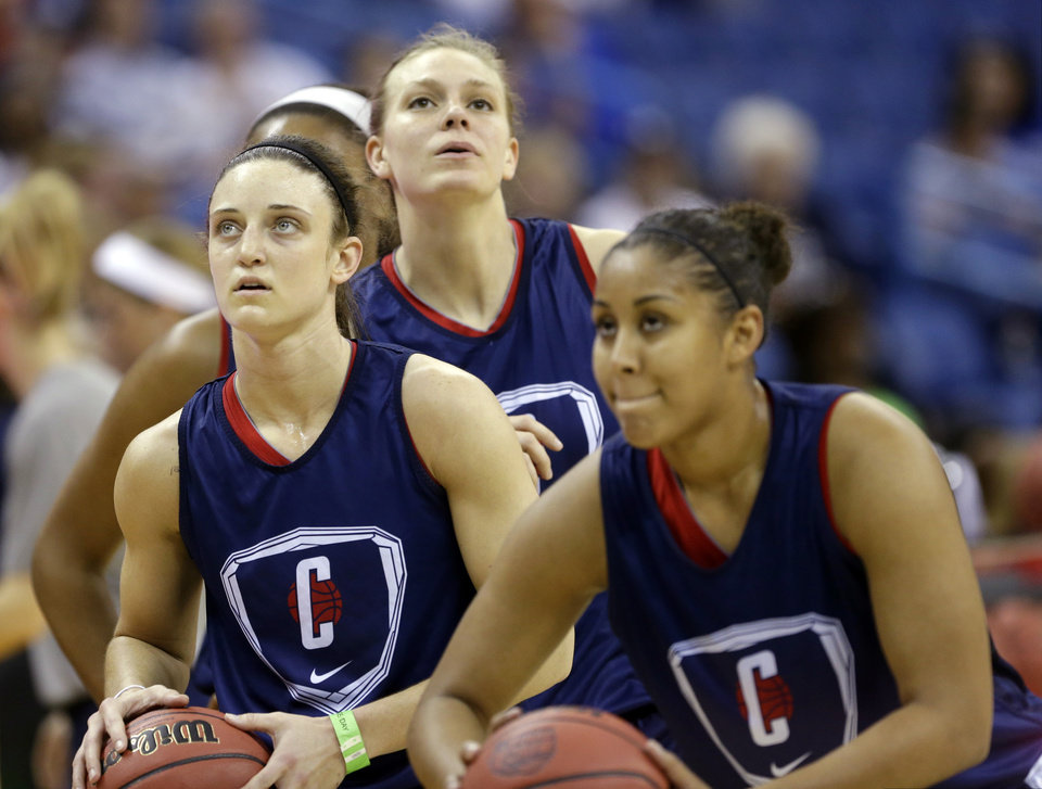 Photo - Connecticut players, from left, Kelly Faris, Heather Buck and Kaleena Mosqueda-Lewis warm up during practice at the Women's Final Four of the NCAA college basketball tournament, Saturday, April 6, 2013, in New Orleans.  UConn plays Notre Dame in a semifinal game on Sunday. (AP Photo/Gerald Herbert)
