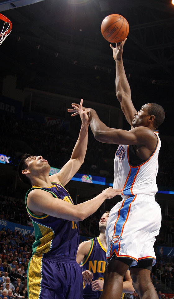 Photo - Oklahoma City's Serge Ibaka (9) shoots over New Orleans' Gustavo Ayon (15) during an NBA basketball game between the Oklahoma City Thunder and the New Orleans Hornets at the Chesapeake Energy Arena in Oklahoma City, Monday, Feb. 20, 2012. Photo by Nate Billings, The Oklahoman