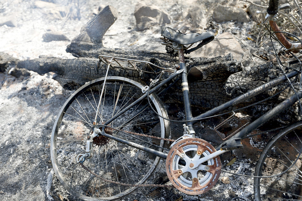 Photo - A bike lies in ash in a burned home, Sunday, Aug. 5, 2012, in Glencoe, Okla., after wildfires moved through the area Saturday. Photo by Sarah Phipps, The Oklahoman