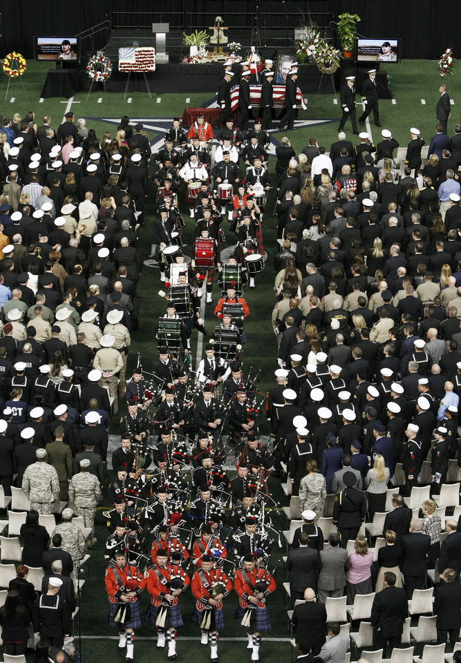 Photo - Bagpipers proceed Christopher Kyle's casket during the recession of a memorial service at Cowboys Stadium, Monday, Feb. 11, 2013, in Arlington, Texas. Thousands attended the public memorial service for Kyle, the former Navy SEAL sniper who was shot to death at a Texas shooting range. (AP Photo/Brandon Wade)