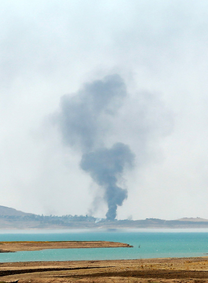 Photo - Smoke rises during airstrikes targeting Islamic State militants at the Mosul Dam outside Mosul, Iraq, Monday, Aug. 18, 2014. Boosted by two days of U.S. airstrikes, Iraqi and Kurdish forces on Monday wrested back control of the country's largest dam from Islamic militants, a military spokesman in Baghdad said, as fighting was reported to be underway for the rest of the strategic facility. (AP Photo/Khalid Mohammed)