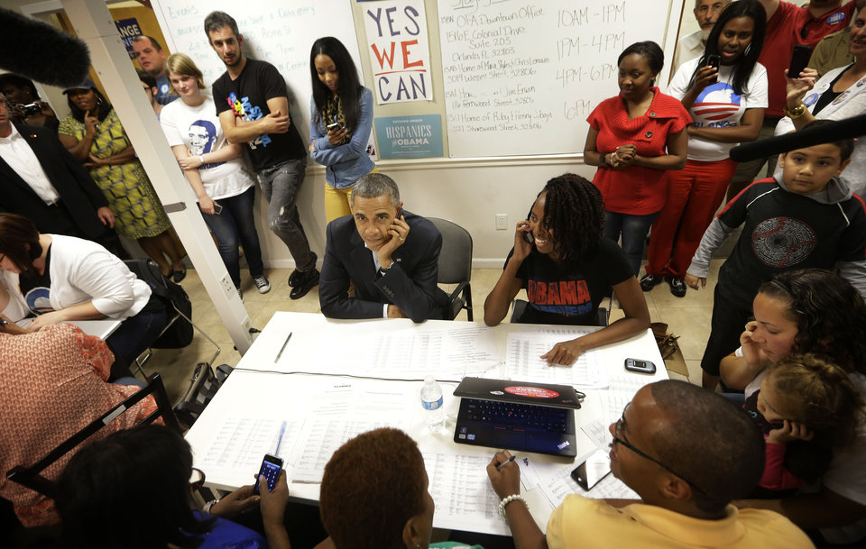 President Barack Obama calls supporters from a local campaign field office during an unscheduled visit to meet volunteers, Sunday, Oct. 28, 2012 in Orlando, Fla. (AP Photo/Pablo Martinez Monsivais)
