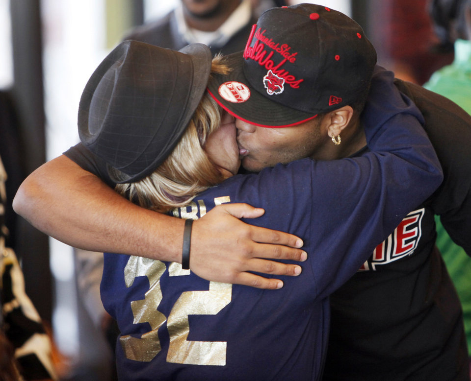 Photo - Heritage Hall's Quintaz Struble gives Jo Ann Struble, his grandmother, a kiss before the National Signing Day ceremony at Heritage Hall in Oklahoma City, Wednesday, Feb. 1, 2012. Struble signed to play football at Arkansas State. Photo by Nate Billings, The Oklahoman
