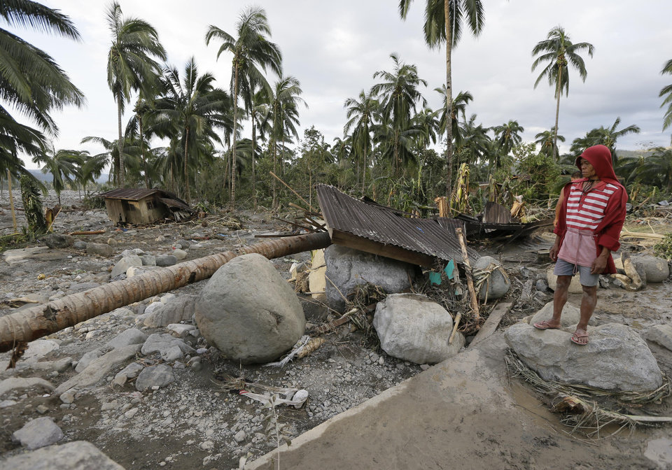 Photo - A resident looks at the devastation brought about by the flash flood that hit the village of Andap, New Bataan township, Compostela Valley in southern Philippines Wednesday Dec. 5, 2012. Typhoon Bopha, one of the strongest typhoons to hit the Philippines this year, barreled across the country's south on Tuesday, killing scores of people while triggering landslides, flooding and cutting off power in two entire provinces. (AP Photo/Bullit Marquez)