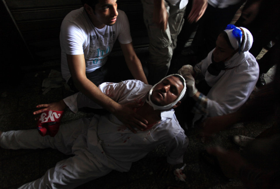 Photo - A wounded Egyptian man receives treatment on the ground during clashes between security forces and supporters of Egypt's ousted President Mohammed Morsi in Ramses Square, near the Al-Fath mosque, in downtown Cairo, Egypt, Friday, Aug. 16, 2013. Gunfire rang out over a main Cairo overpass and police fired tear gas as clashes broke out after tens of thousands of Muslim Brotherhood supporters took to the streets Friday across Egypt in defiance of a military-imposed state of emergency following the country's bloodshed earlier this week. (AP Photo/Khalil Hamra)