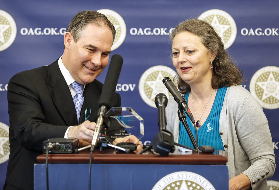 Attorney General Scott Pruitt presents Deana Franke with the Moving Upstream Award for her role in helping victims of sexual assault during a ceremony to advocate Sexual Assault Awareness Month at the Attorney General's office on Monday, April 8, 2013, in Oklahoma City, Okla.