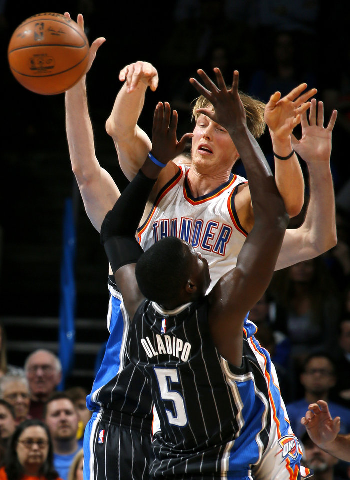 Photo - Oklahoma City's Kyle Singler (5) passes th ball over Orlando's Victor Oladipo (5) during an NBA basketball game between the Oklahoma City Thunder and the Orlando Magic at Chesapeake Energy Arena in Oklahoma City, Wednesday, Feb. 3, 2016. Photo by Bryan Terry, The Oklahoman