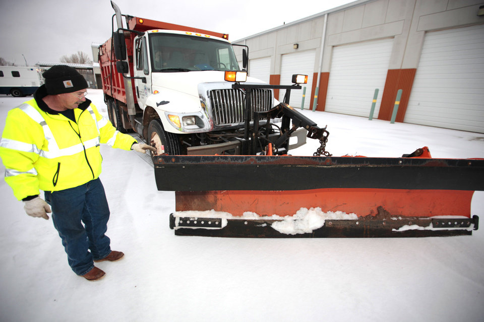 Snowplow driver Larry Fleming checks his plow before heeding out to clears streets in northwest Oklahoma City, Wednesday, December, 4, 2013. Photo by David McDaniel, The Oklahoman