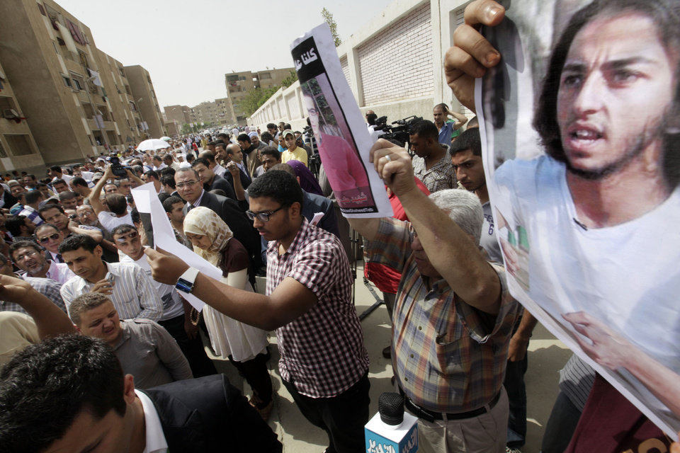 Photo -   Egyptians hold posters showing activists who were killed during clashes following the January 25 revolution, outside a polling station in Cairo, Egypt, Wednesday, May 23, 2012. Poster showing Mina Daniel, a Coptic face of the 25 January Revolution. Nearly a year and a half after the ouster of autocratic leader Hosni Mubarak, millions of Egyptians lined up for hours outside polling stations Wednesday to freely choose a president for the first time in an election that pits old regime figures promising stability against ascending Islamists seeking to consolidate power.(AP Photo/Amr Nabil)