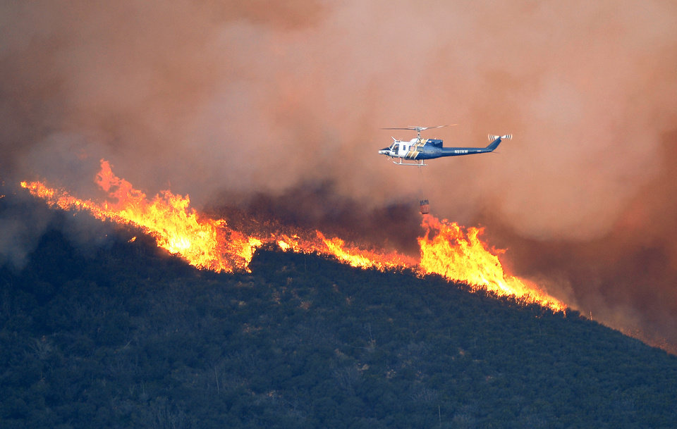 Photo - A water dropping helicopter gets ready to make a drop on a fire burring in Point Mugu State Park during a wildfire that burned several thousand acres, Thursday, May 2, 2013, in Ventura County, Calif.   (AP Photo/Mark J. Terrill)