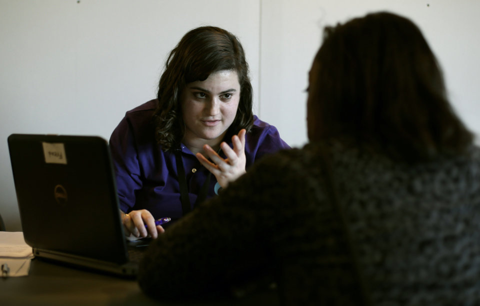 Photo - Elizabeth Rich helps a woman sign up for the Affordable Care Act at Swope Health Services, Monday, March 31, 2014, in Kansas City, Mo. Today is the deadline to sign up for an Affordable Health Care insurance plan however, people who begin the enrollment process but aren't able to complete it by 11:59 p.m. because of a system issue may qualify for a special provision that will allow them to enroll after Monday night. (AP Photo/Charlie Riedel)