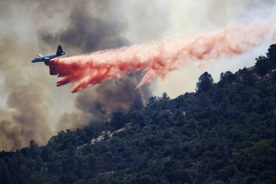 Photo - A bomber drops retardant on a wildfire in Mount Diablo State Park on Monday, Sept. 9, 2013 in Contra Costa County, Calif. A wildfire burning outside Mount Diablo State Park has forced dozens of residents and animals to evacuate Monday. (AP Photo/Marcio Jose Sanchez)