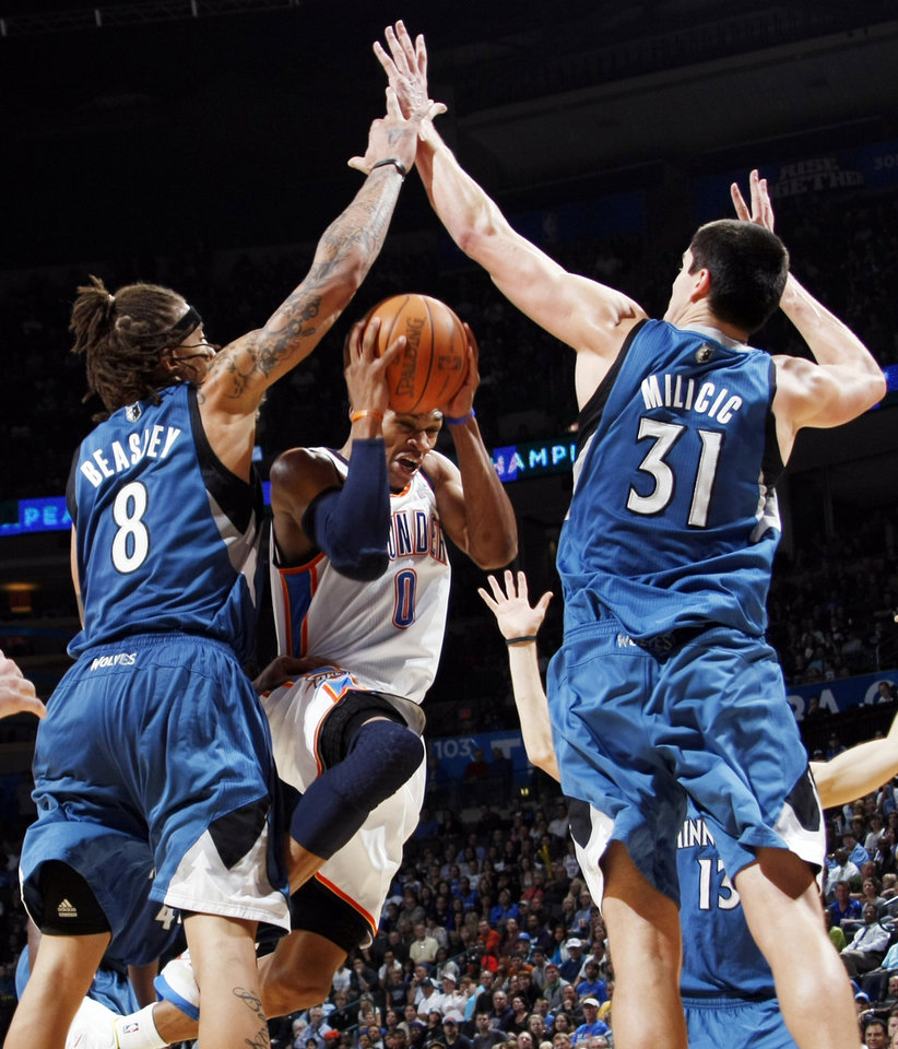 Photo - Oklahoma City's Russell Westbrook (0) tries to get between the defense of Minnesota's Michael Beasley (8) and Darko Milicic (31) during the NBA basketball game between the Minnesota Timberwolves and the Oklahoma City Thunder at the Oklahoma City Arena, Monday, November 22, 2010, in Oklahoma City. The Thunder won, 117-107. Photo by Nate Billings, The Oklahoman