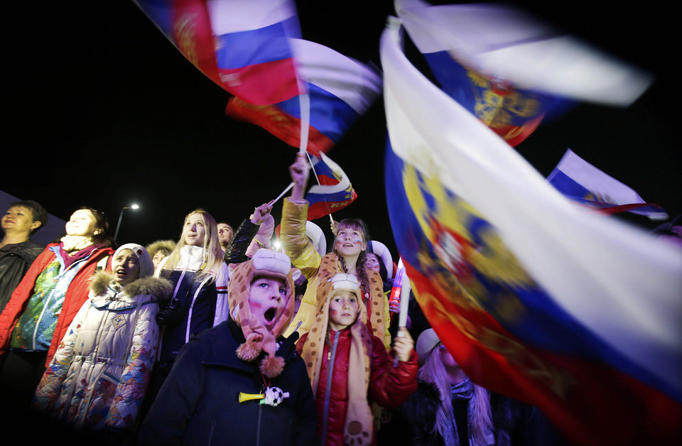 Photo - A Russian child yawns while others wave the national flag as the Russian national anthem is played during the live telecast of the 2014 Winter Olympics opening ceremony, Friday, Feb. 7, 2014, in downtown Sochi, Russia. (AP Photo/Wong Maye-E)