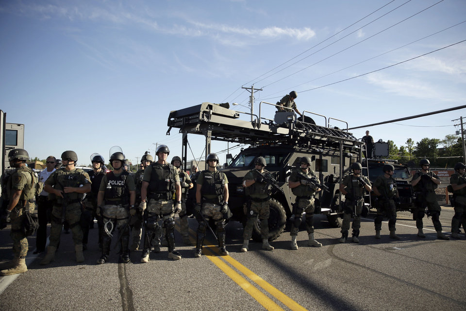 Photo - Police in riot gear watch protesters in Ferguson, Mo. on Wednesday, Aug. 13, 2014. On Saturday, Aug. 9, 2014, a white police officer fatally shot Michael Brown, an unarmed black teenager, in the St. Louis suburb. (AP Photo/Jeff Roberson)