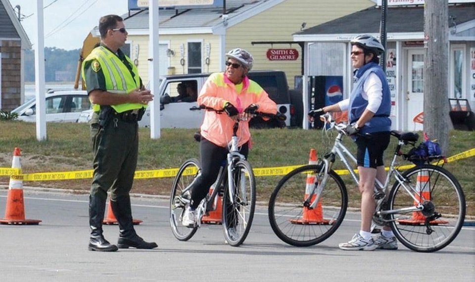 A Hampton, N.H. police officer directs bicyclists to a detour after the Neil R. Underwood Bridge was closed Saturday morning, Sept. 21, 2013 because of a fatal accident involving a car and five bicyclists participating in the Granite State Wheelers Seacoast Century ride. (AP Photo/Portsmouth Herald, Suzanne Laurent)