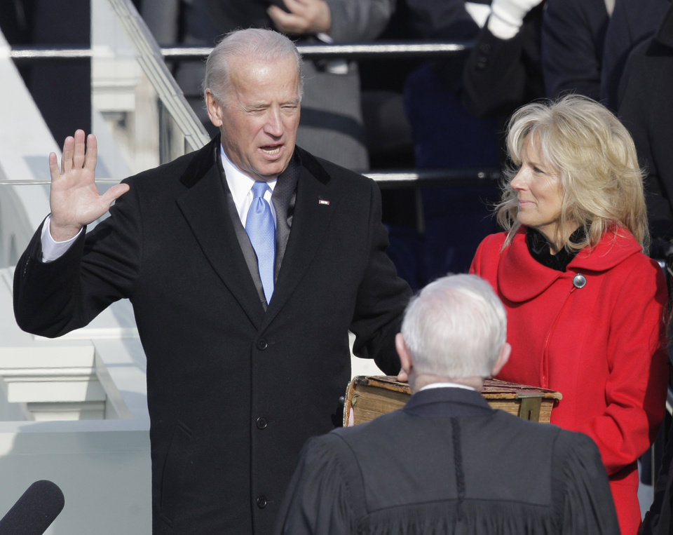 Photo - Vice President-elect Joe Biden, with his wife Jill at his side, takes the oath of office from Justice John Paul Stevens, as his wife holds the Bible at the U.S. Capitol in Washington, Tuesday, Jan. 20, 2009.  (AP Photo/Jae C. Hong)