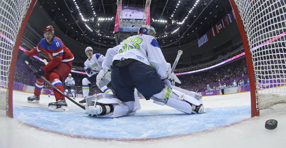 Photo - Russia forward Yevgeni Malkin scores against Slovenia goaltender Robert Kristan in the first period of a men's ice hockey game at the 2014 Winter Olympics, Thursday, Feb. 13, 2014, in Sochi, Russia. (AP Photo/Bruce Bennett, Pool)