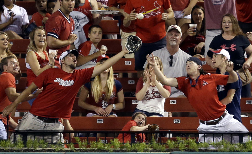 Photo - Fans try to catch a ball hit for a solo home run by St. Louis Cardinals' Allen Craig during the sixth inning of a baseball game against the San Francisco Giants, Thursday, May 29, 2014, in St. Louis. (AP Photo/Jeff Roberson)