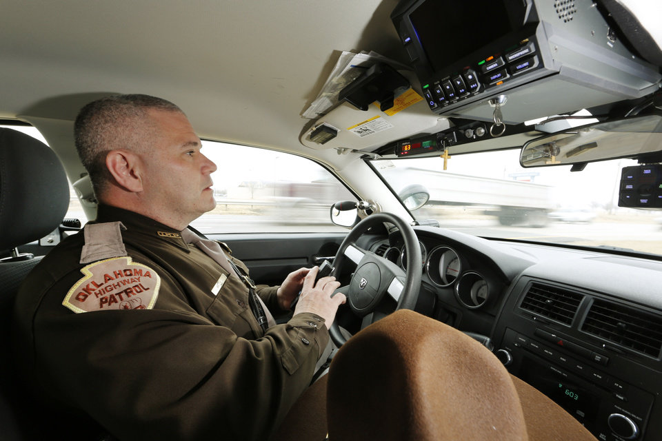 Photo - Oklahoma Highway Patrol trooper Mike Moler looks for speeding motorist on Interstate 240 in Oklahoma City. Photo By Steve Gooch, The Oklahoman  Steve Gooch