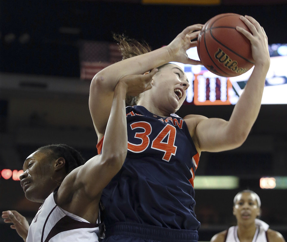 Photo - Auburn center Peyton Davis (34) pulls down a rebound against Texas A&M forward Achiri Ade during the first half in an NCAA college basketball game in the quarterfinals of the Southeastern Conference women's tournament, Friday, March 7, 2014, in Duluth, Ga.(AP Photo/Jason Getz)