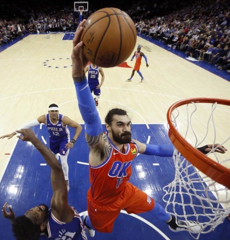 Photo -  Oklahoma City's Steven Adams goes up for a dunk over Philadelphia's Joel Embiid during Monday night's game. Adams scored 24 points and grabbed 15 rebounds in OKC's 120-113 loss. [AP Photo/Matt Slocum]