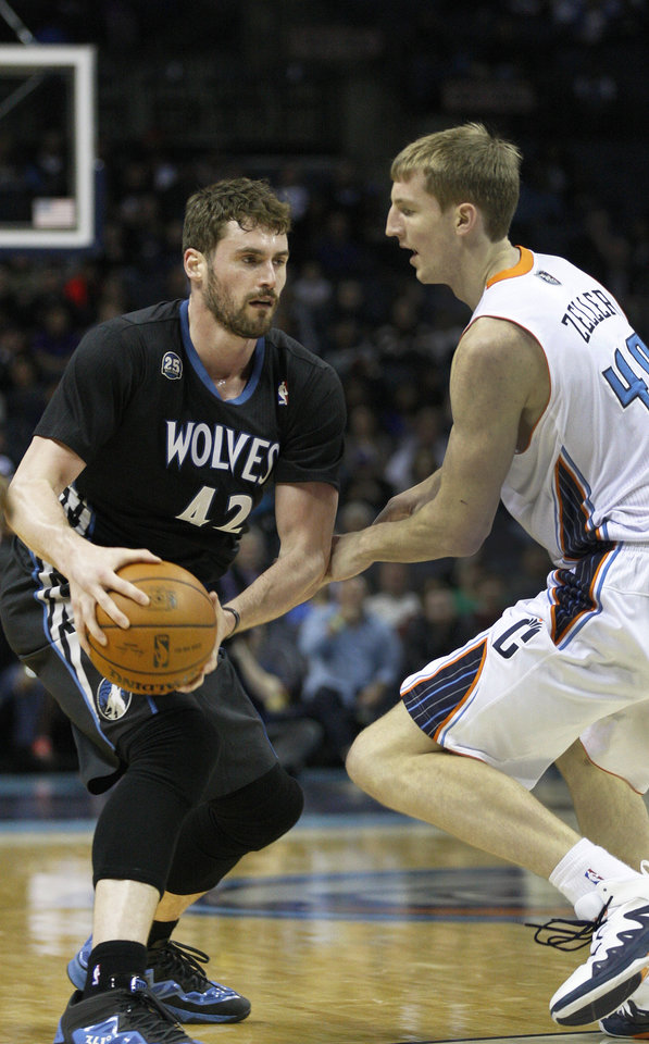Photo - Minnesota Timberwolves forward Kevin Love, right, looks to pass against Charlotte Bobcats center Cody Zeller during the first half of an NBA basketball game in Charlotte, N.C., Friday, March 14, 2014. (AP Photo/Nell Redmond)