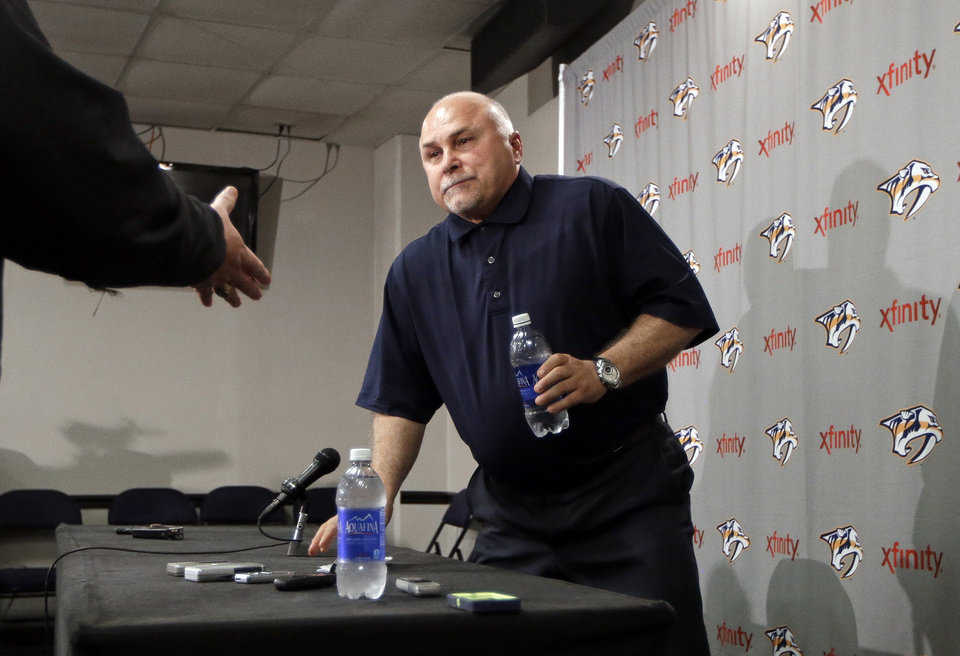 Photo - A well-wisher reaches to shake hands with Nashville Predators coach Barry Trotz as Trotz leaves a news conference Monday, April 14, 2014, in Nashville, Tenn. The Predators announced earlier in the day that Trotz's contract won't be extended and they will begin looking for a new head coach. Trotz is the only head coach the NHL hockey team has had. (AP Photo/Mark Humphrey)