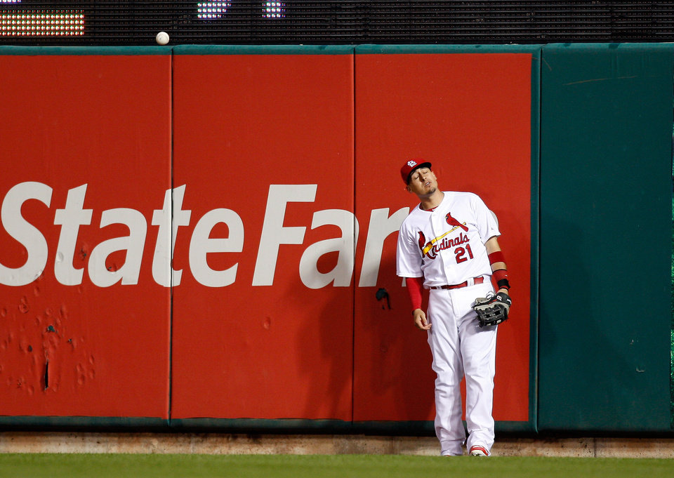 Photo - St. Louis Cardinals right fielder Allen Craig stands at the wall after he was unable to catch a two-run home run hit by Chicago Cubs' Luis Valbuena during the third inning of a baseball game Tuesday, May 13, 2014 , in St. Louis. (AP Photo/Scott Kane)