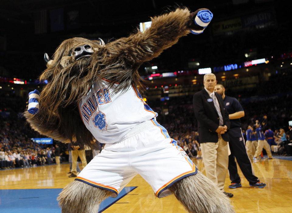 Photo - Thunder mascot Rumble the Bison throws t-shirts to the crowd during an NBA basketball game between the New York Knicks and the Oklahoma City Thunder at Chesapeake Energy Arena in Oklahoma City, Sunday, Feb. 9, 2014. Oklahoma City won, 112-100. Photo by Nate Billings, The Oklahoman