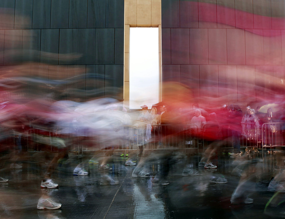 Photo - A slow shutter speed shows runners passing by the 9:03 gate on the west side of the Oklahoma City National Memorial and Museum during the 11th Annual Oklahoma City Memorial Marathon in Oklahoma City on Sunday, May 1, 2011. Photo by John Clanton, The Oklahoman