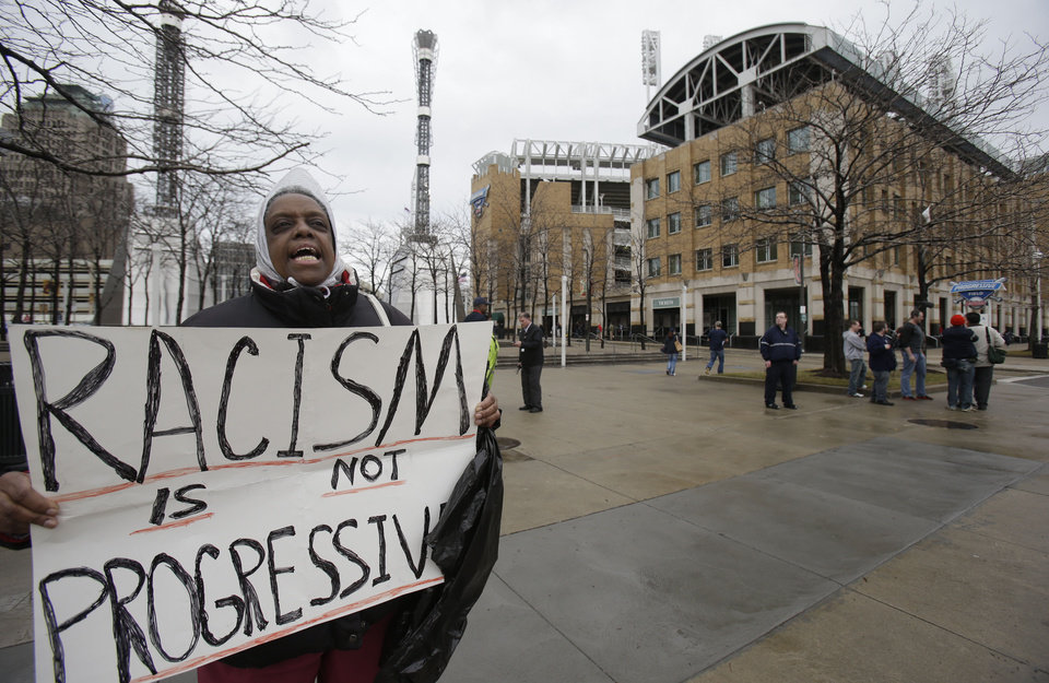 Terri A.Tolefree protests the Cleveland Indians use of Chief Wahoo as fans enter the Progressive Field, right, before a baseball game between the Minnesota Twins and the Cleveland Indians, Friday, April 4, 2014, in Cleveland. (AP Photo/Tony Dejak)