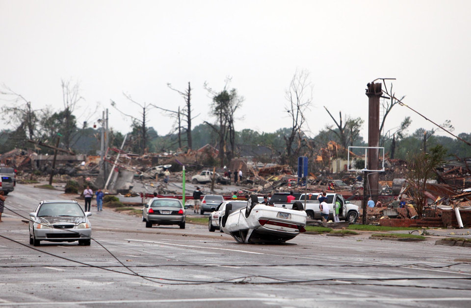 Photo - Cars are flipped and buildings are destroyed along 15th St. and the surrounding neighborhoods in Tuscaloosa, Ala. Wednesday, April 27, 2011. A wave of severe storms laced with tornadoes strafed the South on Wednesday, killing at least 16 people around the region and splintering buildings across swaths of an Alabama university town. (AP Photo/The Tuscaloosa News, Dusty Compton)